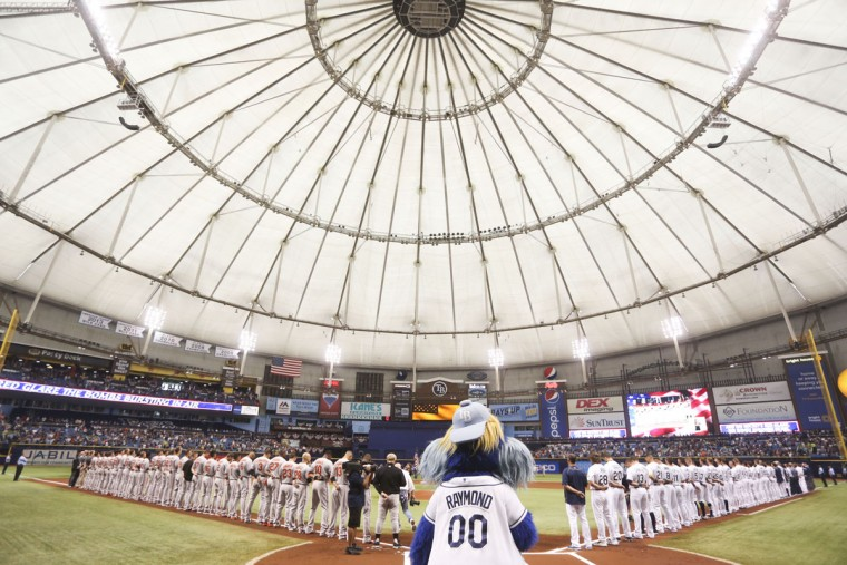 The Baltimore Orioles and Tampa Bay Rays line up during the National Anthem before the Rays' home opener at Tropicana Field in St. Petersburg on Monday, April 6, 2015. (AP Photo/Tampa Bay Times/Eve Edelheit)