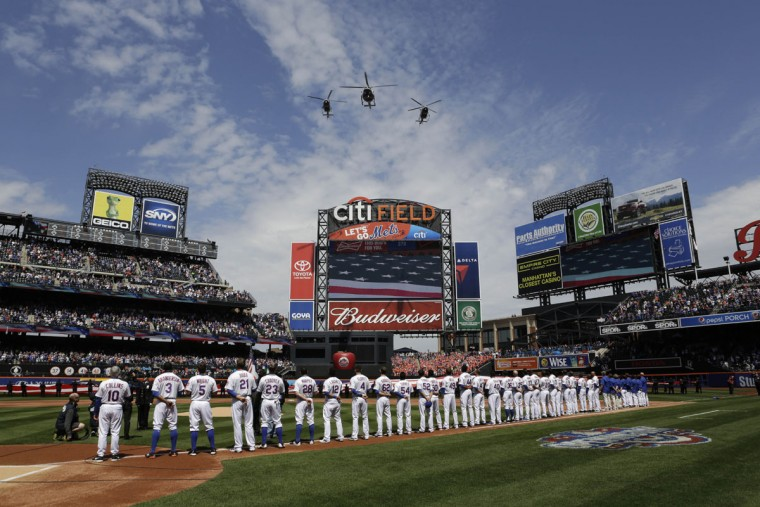 Three helicopters in formation fly over CitField as members of the New York Mets stand at attention before the start of the Mets home opening baseball game against the Philadelphia Phillies in New York, Monday, April 13, 2015. (AP Photo/Kathy Willens)