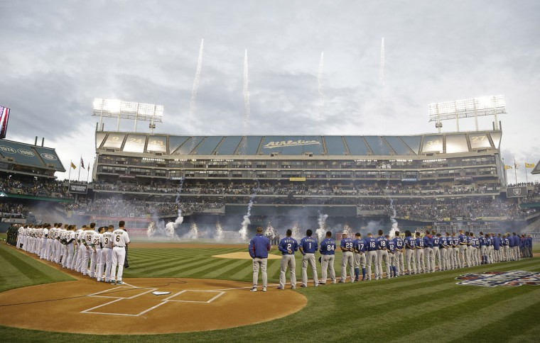 The Oakland Athletics, left, and Texas Rangers, right, stand along the baselines and watch opening day fireworks before the start of the A's home opener Monday, April 6, 2015, in Oakland, Calif. (AP Photo/Eric Risberg)