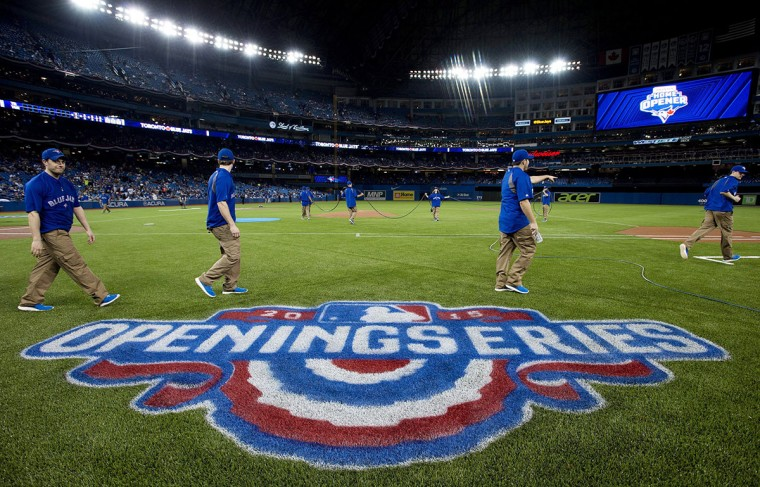 Toronto Blue Jays grounds crew members prepare the field for the Blue Jays' home-opener baseball game against the Tampa Bay Rays on Monday, April 13, 2015, in Toronto. (Nathan Denette/The Canadian Press via AP)
