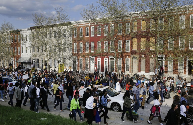 Protestors march to the Baltimore Police Department's Western District police station during a march and vigil for Freddie Gray, Tuesday, April 21, 2015, in Baltimore. Gray died from spinal injuries a week after he was arrested and transported in a police van. (AP Photo/Patrick Semansky)