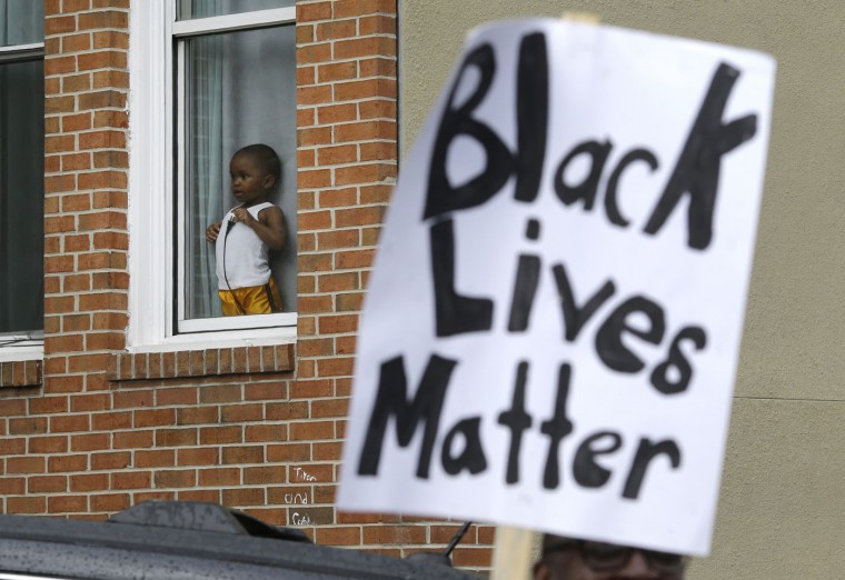 A child watches a protest march for Freddie Gray as it passes by, Wednesday, April 22, 2015, in Baltimore. Gray died from spinal injuries about a week after he was arrested and transported in a police van. (AP Photo/Patrick Semansky)