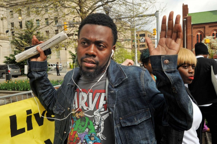 """William Stewart, a friend of Freddie Gray, protests outside City Hall in Baltimore, Monday, April 20, 2015. Baltimore's top police officials, mayor and prosecutor sought to calm a """"community on edge"""" Monday while investigating how Gray suffered a fatal spine injury while under arrest. Six officers have been suspended, but investigators say they still don't know how it happened. (Amy Davis/The Baltimore Sun via AP)"""