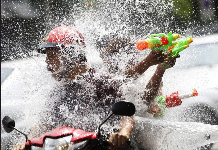 People riding on a motorbike react as a boy splashes water on them during traditional Thai New Year celebrations or Songkran water festival in Bangkok Monday, April 13, 2015. (AP Photo/Sakchai Lalit)