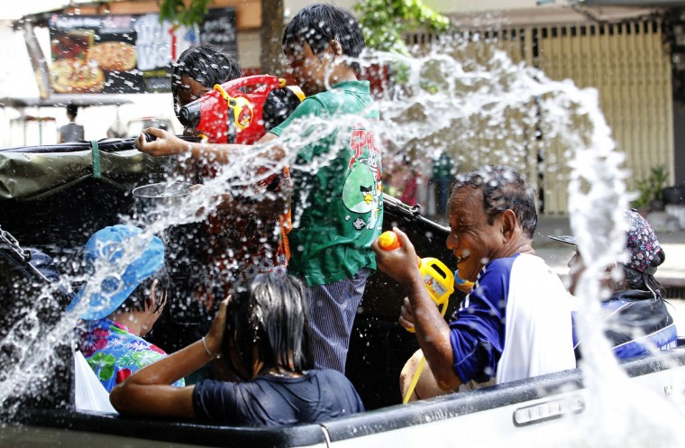 People on the back of a truck react as a bucket of water is thrown on them during a traditional Thai New Year celebrations or Songkran water festival in Bangkok Monday, April 13, 2015. (AP Photo/Sakchai Lalit)