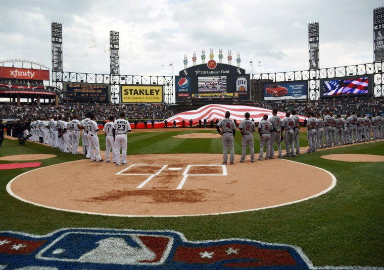 Players stand during the national anthem before the White Sox home opener against the Minnesota Twins, Friday, April 10, 2015, in Chicago. (AP Photo/David Banks)