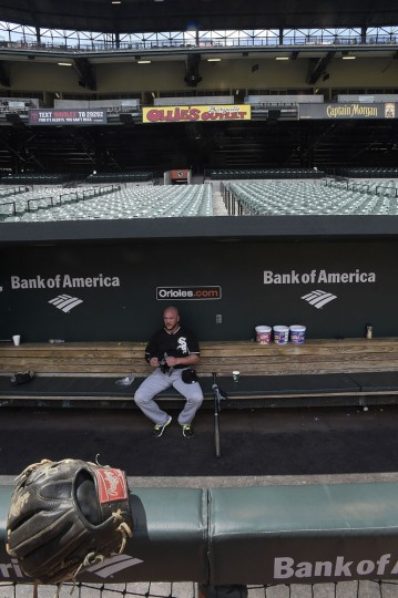 Chicago White Sox catcher Tyler Flowers sits in the dugout of an empty stadium before playing the Baltimore Orioles in a baseball game, Wednesday, April 29, 2015, in Baltimore. Due to security concerns the game was closed to the public. (AP Photo/Gail Burton)