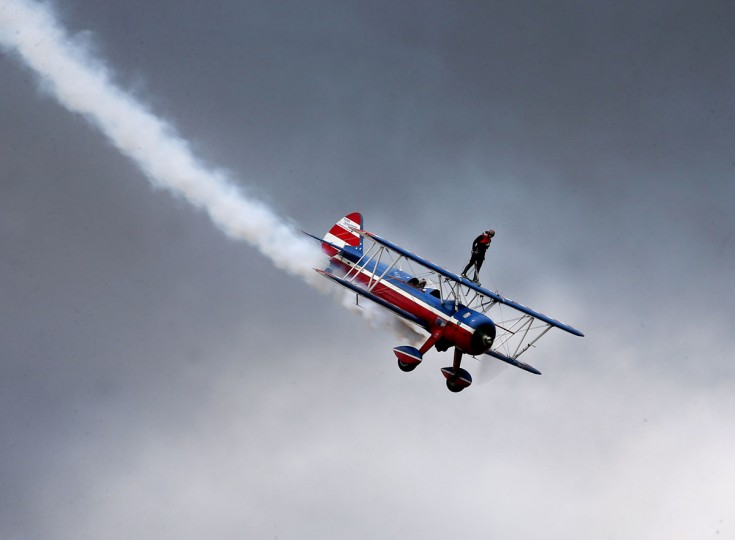 Wing walker Ashley Battles stands atop a biplane during the Gulf Coast Salute Air Show, Sunday, April 12, 2015 at Tyndall Air Force Base in Panama City, Fla. (Patti Blake/News Herald via AP)