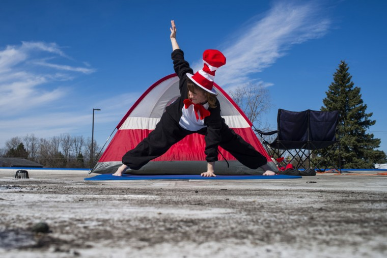 Principal Dianne Coplin performs yoga as she works from atop the school dressed as the Cat in the Hat, Tuesday, April 14, 2015, at Colonel Donald McMonagle Elementary in Mt. Morris Township, Mich. Students at the school read 6,693 books, exceeding their reading month goal of 5,000, resulting in Coplin dressing as the famous Dr. Seuss character. (Jake May/The Flint Journal-MLive.com via AP)