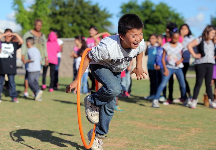 Nine-year-old Alejandro Henderson jumps through a hula hoop during a game Tuesday April 14, 2015 at the ROCrageous Sidewalk Ministry at La Promesa Apartments in Odessa, Texas. The sidewalk ministry is an outreach program for Housing and Urban Development housing sites around Odessa which promotes worship and offers a full service while participating in games with the children in the housing areas. (Edyta Blaszczyk/Odessa American via AP)