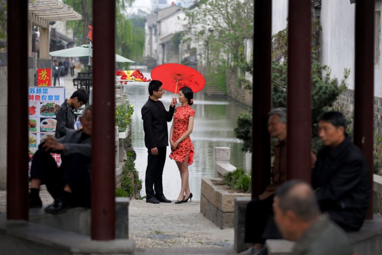 Residents take rest at a pavilion as a bride and groom, dressed a traditional costume, pose for wedding photos near Pingjiang steet in Suzhou in east China's Jiangsu province, Thursday, April 16, 2015. Pingjiang street was built along a canal and existed as early as the Song Dynasty, and is one of the famous tourist attractions in the country. (AP Photo/Andy Wong)