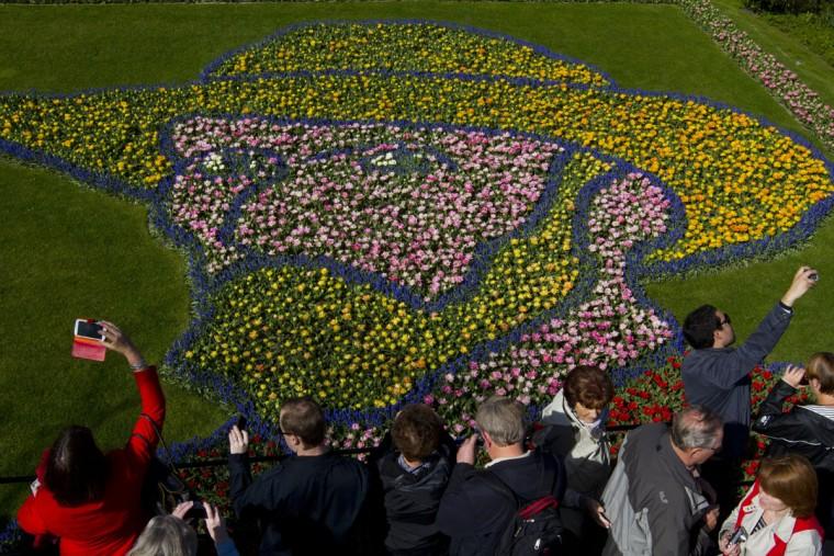 Tourists take pictures of a floral arrangement depicting Dutch master Vincent van Gogh at Keukenhof, a spring park with approximately seven million flower bulbs, in Lisse, Netherlands, Tuesday, April 21, 2015. (AP Photo/Peter Dejong)