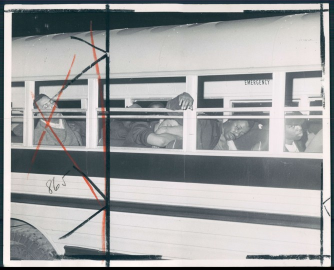 Curfew violation suspects sleep in a parked bus awaiting their trials in the morning. Lloyd Pearson, Sun