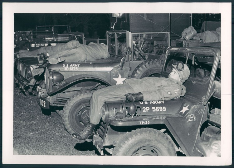 National Guard soldiers asleep on the hoods of jeeps in Druid Hill Park.