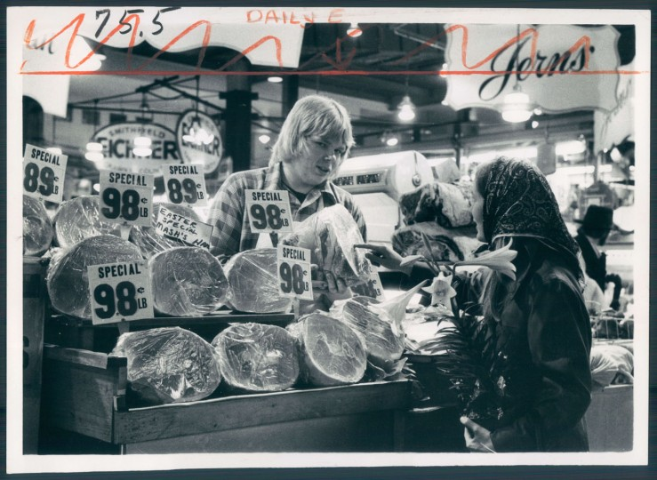 April 11, 1974 - Easter lily in hand, Martha Glaze picks out a ham at Lexington Market for her holiday dinner. Salesperson is John A. Regan. Photo taken by (Baltimore Sun Staff Photographer Ralph L. Robinson)