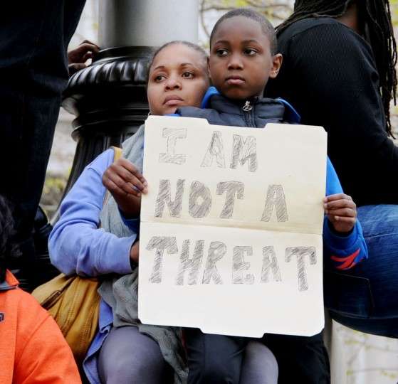 "Maurina Richardson-Frierson, Edgewater, and her son, Amir Frierson, 9, watch the rally at City Hall from an elevated position. Amir holds a sign that reads ""I Am Not A Threat"" that was created by his father. March from Mount Street and Presbury Streets in Sandtown/WInchester where Freddie Gray was arrested to CIty Hall to and rally related to protest the death of Gray in police custody. (Kim Hairston/The Baltimore Sun)"