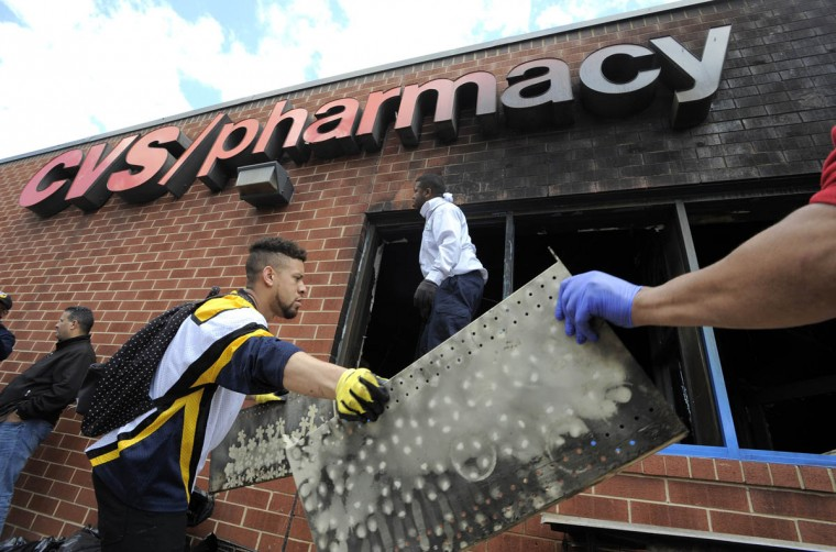 Volunteers work to help clear out the debris from the CVS on North Avenue that caught fire last night. Protesters gather at the intersection of Pennsylvania Avenue and North Avenue today a day after riots broke out in Baltimore over the death of Freddie Gray. (Lloyd Fox/Baltimore Sun)