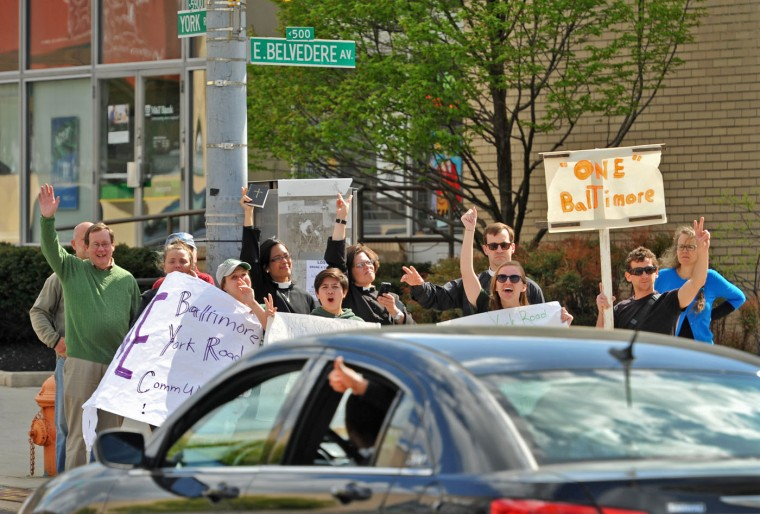 A passenger in a car crossing Belvedere Avenue at York Road gives a thumbs up to a group from The York Road Partnership who gathered to rally for peace and justice on York Road between Woodbourne Avenue and East Northern Parkway. The rallies followed a morning cleanup by Loyola University students and others at several stores along York Road near Woodbourne Avenue that had been looted Monday night. Some stores that had been looted were closed. (Amy Davis/Baltimore Sun)