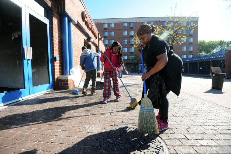 Left to right, Ishawn Nelson, 12, his sister, Marae Nelson, 9, sweep the area outside the CVS on North and Pennsylvania Avenues. The store was looted and set on fire on Monday night during a riot. (Kim Hairston/The Baltimore Sun)
