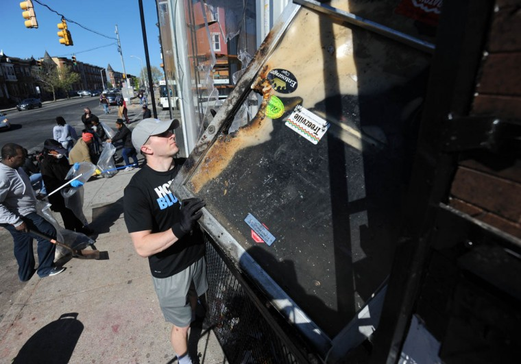 Volunteers remove debris from outside the E-Z Mart Tobacco and Convenience Store on North and Fulton Avenues. It is one of the stores hit by rioters Monday night. (Kim Hairston/The Baltimore Sun)