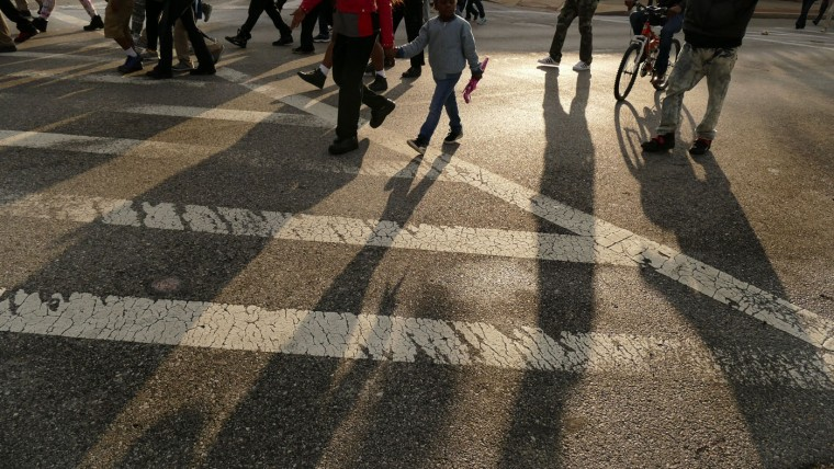 The sun casts long shadows as people walk on Pennsylvania Avenue toward Martin Luther King Jr. Blvd, as marchers take to the streets for another day of protests over the death of local resident Freddie Gray, while in police custody. (Karl Merton Ferron/Baltimore Sun)