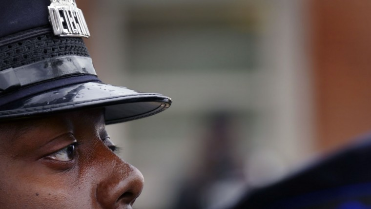 A Baltimore Police detective watches from behind the expanded barrier of the Western District police station as marchers take to the streets for another day of protests over the death of local resident Freddie Gray, while in police custody. (Karl Merton Ferron/Baltimore Sun)