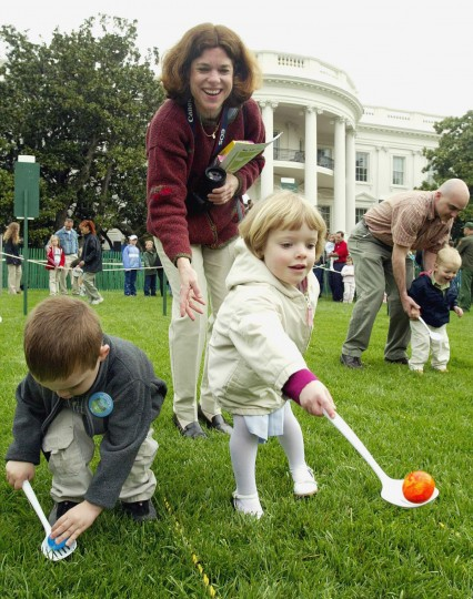 Katherine Dryer, center, watches, Monday, April 21, 2003, as her daughter Maggie Dryer, 3, right, and Ethan Frietze, left, take part in the annual Easter Egg Roll at the White House. This year only military families were allowed to attend the event. Dryer's husband is stationed on the hospital ship USS Comfort. President Bush and wife Laura return later from a Easter weekend stay at the Crawford, Texas, ranch. Others are unidentified. (AP Photo/Ron Edmonds)