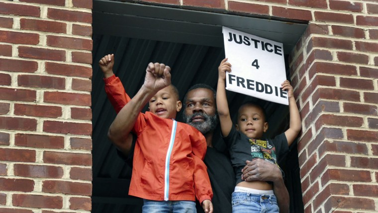 Michael Pulley with his two 4-year-old grandsons watch from a second floor balcony in support of the family as residents return from a march to the Western District of the Baltimore Police following the death of local resident Freddie Gray on Tuesday, April 21, 2015. (Karl Merton Ferron/Baltimore Sun)