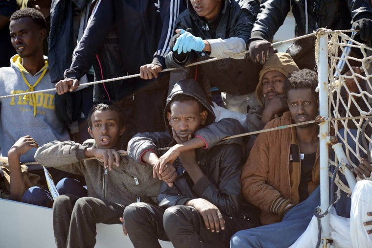 Migrants wait to disembark from the Italian Navy vessel 'Chimera' in the harbor of Salerno, Italy. Italy pressed the European Union on Wednesday to devise concrete, robust steps to stop the deadly tide of migrants on smugglers' boats in the Mediterranean, including setting up refugee camps in countries bordering Libya. Italian Defense Minister Roberta Pinotti also said human traffickers must be targeted with military intervention. (Francesco Pecoraro/AP photo)