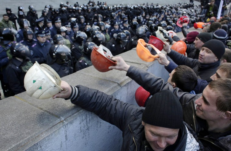 """Ukrainian coal miners protest outside the Government building in Kiev demanding the government protect their jobs as the eastern separatist conflict threatens to force pits to close. Banging their helmets, the miners yelled """"Shame"""" on the pro-western government, demanding it raise their pay and restore subsidies to the mines that help power the Ukrainian industry. (Anatolii Stepanov/AFP/Getty Images)"""
