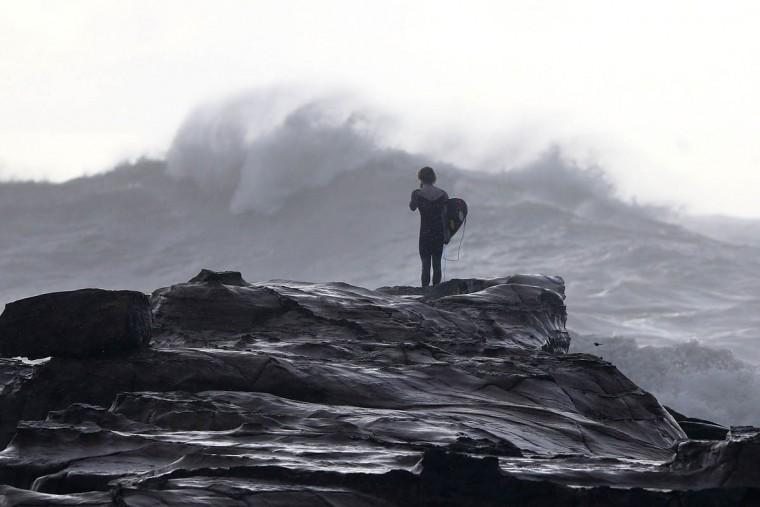 A surfer watches turbulent seas at Avoca Beach on the Cntral Coast in Sydney, Australia. Three people have died and more than 200,000 are still without power as cyclonic winds and rains continue to lash the Sydney, Hunter Valley and Central Coast regions of New South Wales. (Tony Feder/Getty Images)