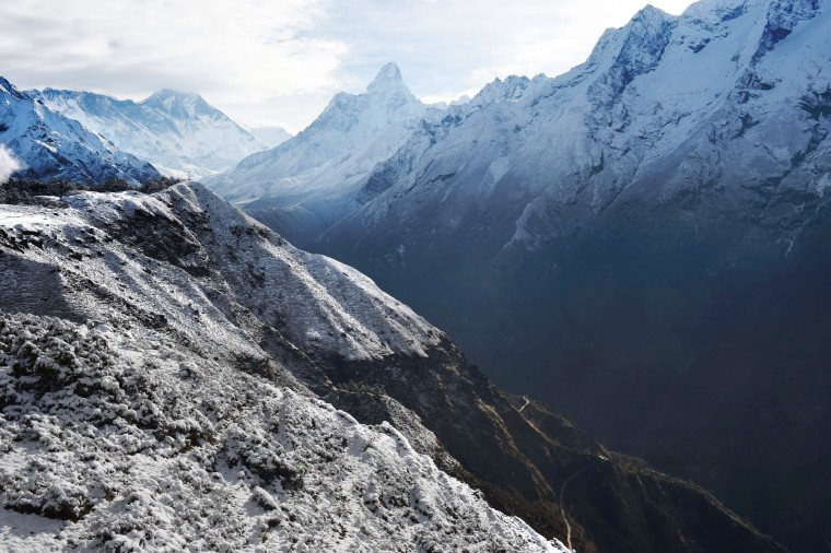 A trekking path (lower right) is dwarfed by high-altitude peaks including Ama Dablam (center) in a valley leading north into Nepal's Khumbu region, which is home to Mt. Everest. This region is flooded by hikers and climbers this time of the year. (Roberto Schmidt/AFP-Getty Images)