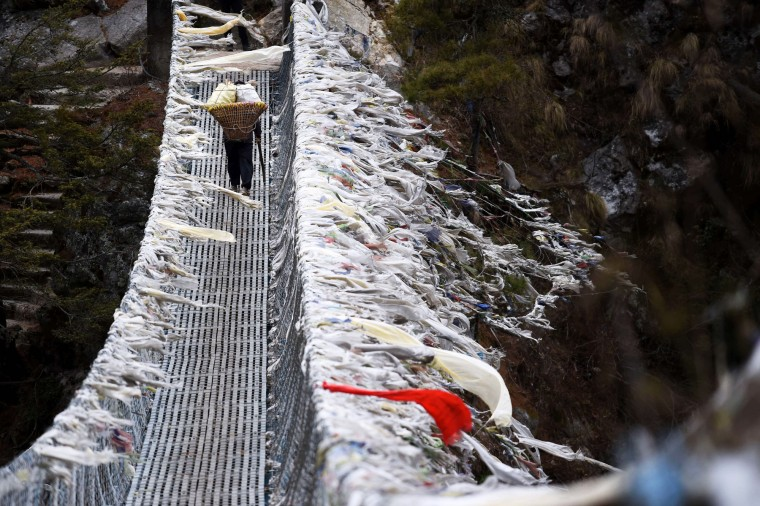A Nepali porter walks across a suspension bridge over a deep valley near Labja Dorhan on his way to the north-eastern town of Namche Bazar. In the Himalayan town of Lukla, excitement mingles with fear as mountaineers make their way up to Everest a year after an avalanche killed 16 guides and triggered an unprecedented shut-down of the world's highest peak. Some are returning after being forced to abandon their attempt on the summit in 2014 during the chaos and recriminations that followed the deadliest disaster ever to hit Everest. (Roberto Schmidt/AFP-Getty Images)
