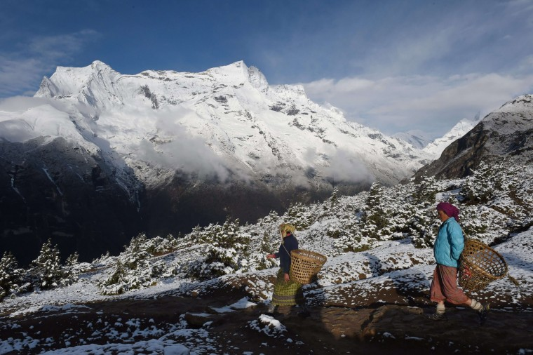 Nepalese villagers decend from higher elevations above the town of Namche Bazar as they head to market day in town to purchase merchandise they will take back to their village for resale. (Roberto Schmidt/AFP-Getty Images)
