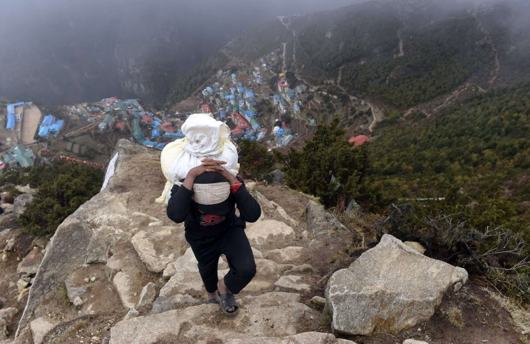 Nepali porter Milan Rai, 14, starts his trek on a rocky path high above the north-eastern town of Namche Bazar on his way to making a delivery to a hotel in a nearby town at higher elevation. (Roberto Schmidt/AFP-Getty Images)