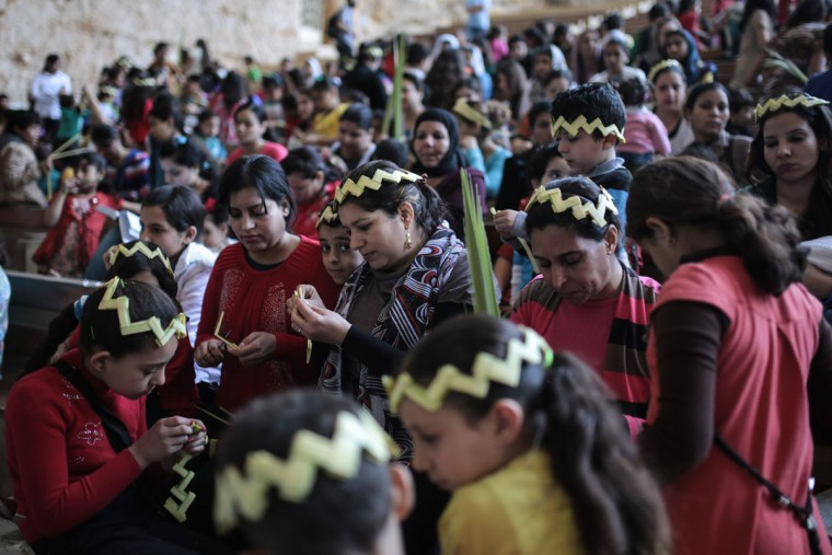 Egyptian Orthodox Christians weave palm fronds during a service to celebrate Palm Sunday in the Samaan el-Kharaz Church in the Mokattam district of Cairo, Egypt, Sunday, April 5, 2015. For Christians worldwide, Palm Sunday marks Jesus Christ's entrance into Jerusalem, when his followers laid palm branches in his path, prior to his crucifixion. Western Christian churches and most Orthodox Christian churches follow different calendars and observe Easter on different dates. (AP Photo/Mosa'ab Elshamy)