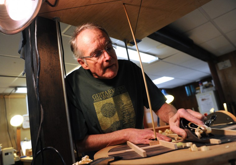 Luthier David MacCubbin works on the back struts of a guitar he's assembling in the basement of his Cockeysville home on Thursday, March 19, 2015. MacCubbin has been hand-making and selling acoustic guitars for nearly 15 years. (Jon Sham/BSMG)