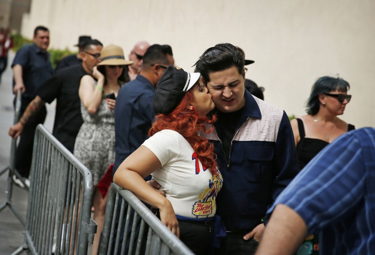 In this April 5, 2015, photo, Angie Almilla kisses Eric Martinez while waiting in line for a pool party at the Viva Las Vegas Rockabilly Weekend in Las Vegas. The event included fashion shows, dance lessons and contests set against a backdrop of rock 'n roll and pre-1963 classic cars. (AP Photo/John Locher)