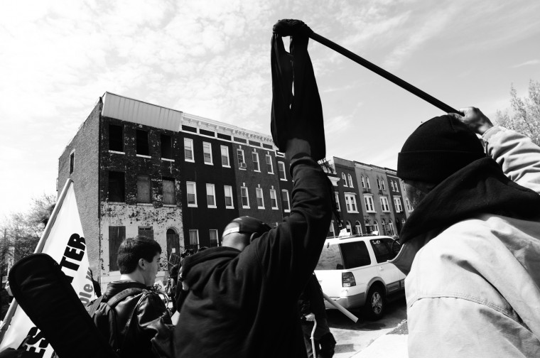 """April 25: A man holds up a """"mourning cloth"""" for Freddie Gray during the march downtown. BCPD tweet: We are listening to the concerns of the community while protecting their constitutional rights to protest and be heard. #WeHearYou See more photos from the day here."""