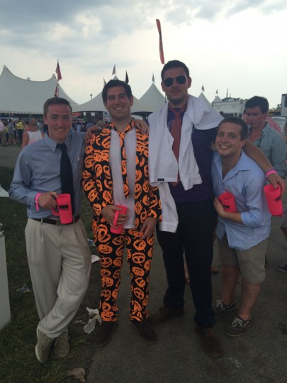 "Peter Martin, 23, poses with his friends in his pumpkin suit. ""Who else is going to be wearing a Halloween suit at Preakness?"" Martin, who lives in Reisterstown said. As for sporting a polyester suit in sweltering heat, ""It's not been enjoyable,"" the ""Pumking"" said. (Quinn Kelley/Baltimore Sun)"
