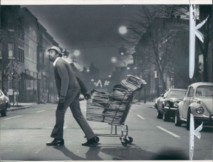 "03/17/1980: Work time comes early for ""Big Jim"" Johnson, who distributes the Sunday editions of The Sun and the News American. Here, he walks in the pre-dawn light near his home in the 2000 block of McColloh street."