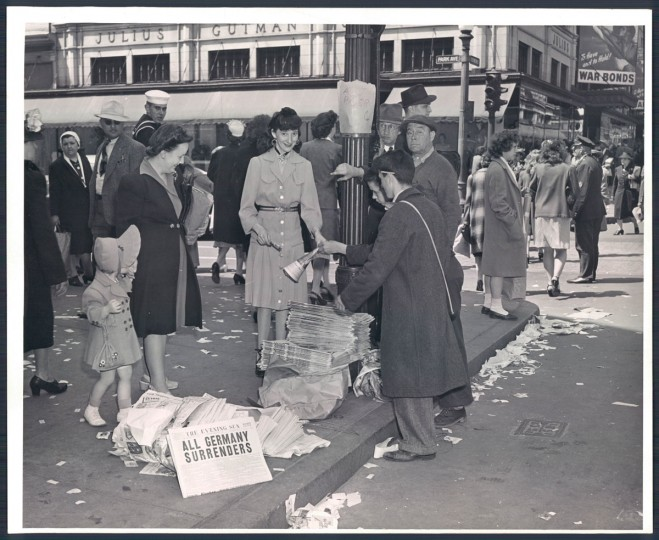 """Newspapers sold for 5 cents at Park Avenue and Lexington Street. Headline: """"All Germany Surrenders."""" (A. Aubrey Bodine/Baltimore Sun archives)"""