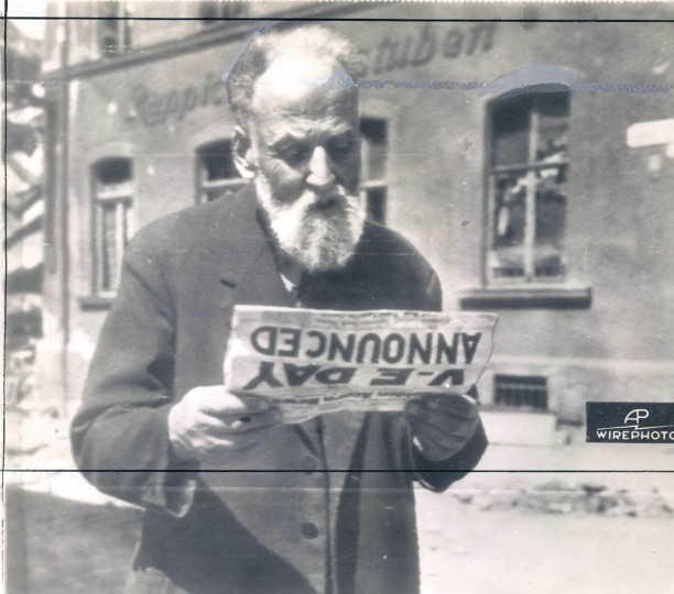 """This bearded German civilian at Falkenstein, Germany, on May 8, reads of complete surrender of his country's forces in the """"Golden Acorn,"""" paper of the 87th Infantry Division of the U.S. 1st Army. (AP Wirephoto from Signal Corps RadioPhoto from London)"""