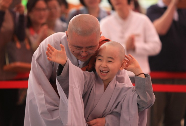 A child rubs his head after a Buddhist monk shaved his hair off during the 'Children Becoming Buddhist Monks' ceremony forthcoming buddha's birthday at a Chogye temple on May 11, 2015 in Seoul, South Korea. Children have their hair shaved off during the 'Children Becoming Buddhist Monks' ceremony ahead of buddha's birthday at a Chogye temple. The children will stay at the temple to learn about Buddhism for 14 days. Buddha was born approximately 2,559 years ago, and although the exact date is unknown, Buddha's official birthday is celebrated on the full moon in May in South Korea, which is on May 25 this year. (Photo by Chung Sung-Jun/Getty Images)