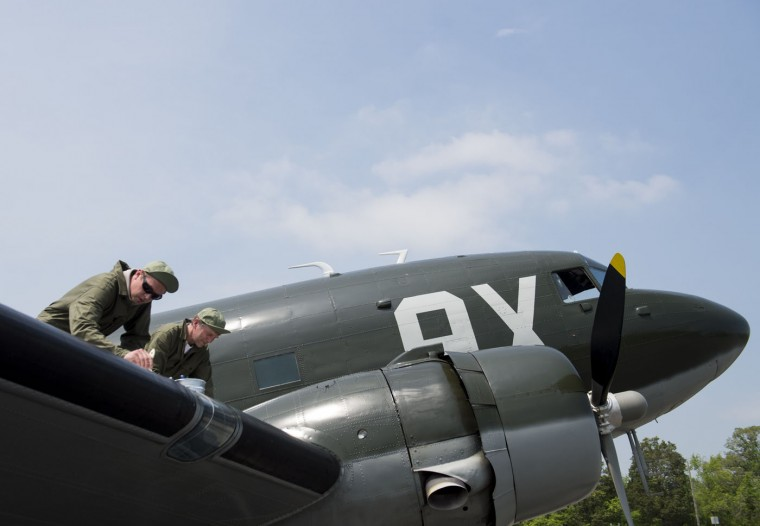 Eric Trueblood (L) and Nick Knobil (R), with the Texas Flying Legends Museum, paint stripes on a Douglas C-53 Skytrooper airplane as dozens of World War II era aircraft gather at Culpeper Regional Airport in Brandy Station, Virginia, May 7, 2015. The planes will fly past the National Mall in Washington, DC, on May 8, during the Arsenal of Democracy World War II Victory Capitol Flyover to commemorate the 70th anniversary of Victory in Europe (VE) Day. (Saul Loeb/AFP/Getty Images)