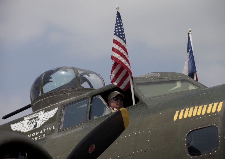 A B-17 bomber crew member looks out of the cockpit window after a practice flight with dozens of World War II era aircraft at Manassas Regional Airport, Virginia, May 7, 2015. Dozens of World War II era planes will fly past the National Mall in Washington, DC, on May 8, during the Arsenal of Democracy World War II Victory Capitol Flyover to commemorate the 70th anniversary of Victory in Europe (VE) Day. (Andrew Caballero-Reynolds/AFP/Getty Images)