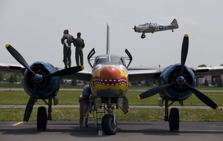 Airplane crew members check their engines as another plane lands after a practice flight with dozens of World War II era aircraft at Culpeper Regional Airport in Brandy Station, Virginia, May 7, 2015. Dozens of World War II era planes will fly past the National Mall in Washington, DC, on May 8, during the Arsenal of Democracy World War II Victory Capitol Flyover to commemorate the 70th anniversary of Victory in Europe (VE) Day. (Andrew Caballero-Reynolds/AFP/Getty Images)
