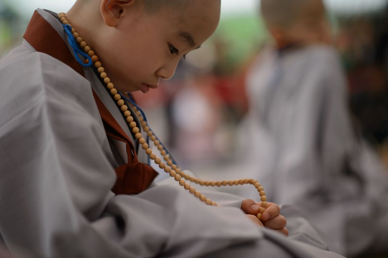 A young novice monk holds his new prayer beads after having his head shaved by Buddhist monks during a ceremony entitled 'Children Becoming Buddhist Monks', at the Jogye temple in Seoul on May 11, 2015. Following the ceremony the children stay at the temple where they are taught about Buddhism, for two weeks, until Buddha's birthday on May 25. (AFP Photo/Ed Jones)