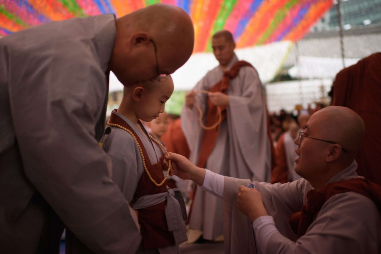 A young novice monk (C) is presented with prayer beads after having his head shaved by Buddhist monks during a ceremony entitled 'Children Becoming Buddhist Monks', at the Jogye temple in Seoul on May 11, 2015. Following the ceremony the children stay at the temple where they are taught about Buddhism, for two weeks, until Buddha's birthday on May 25. (AFP Photo/Ed Jones)