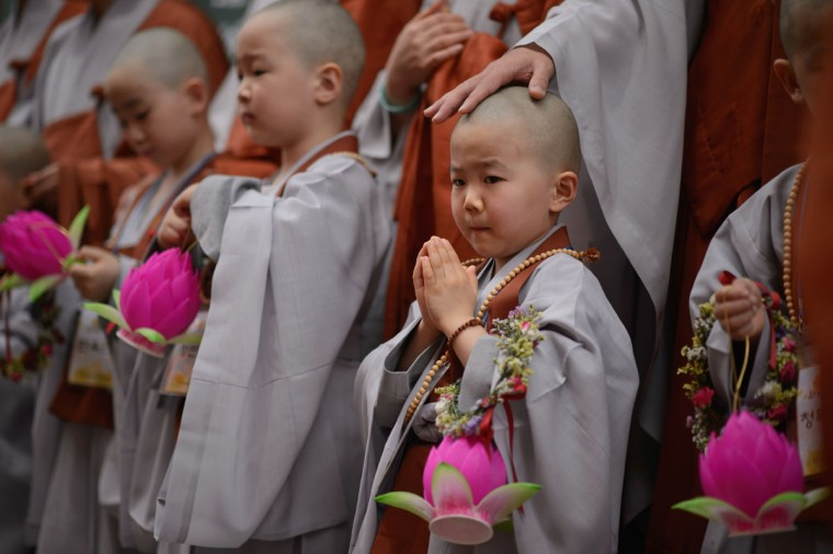 Young novice gather having their heads shaved by Buddhist monks during a ceremony entitled 'Children Becoming Buddhist Monks', at the Jogye temple in Seoul on May 11, 2015. Following the ceremony the children stay at the temple where they are taught about Buddhism, for two weeks, until Buddha's birthday on May 25. (AFP Photo/Ed Jones)